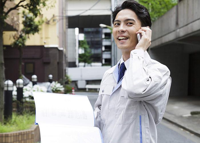 書類を持ちながら通話中の男性
