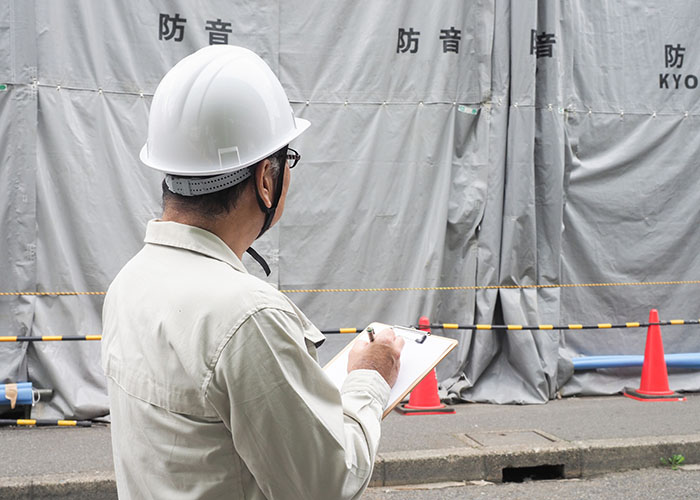 工事現場の前でメモをとっている男性